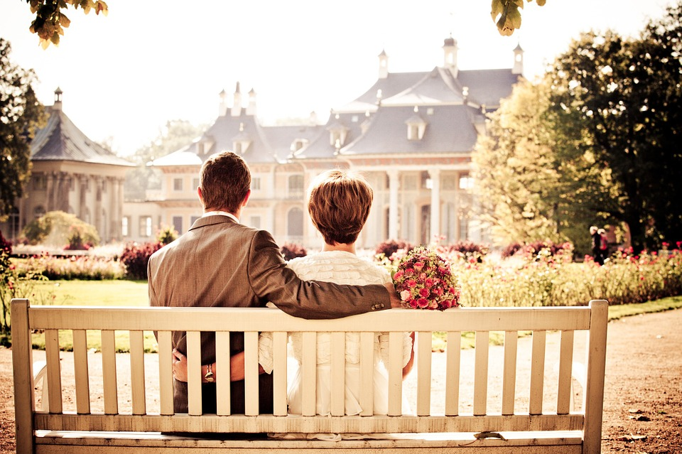older bride and groom on park bench